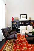 Black armchairs, pale sofa and black sideboard in elegant lounge