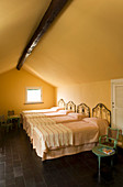 Four wrought iron single beds in attic room with black-tiled floor