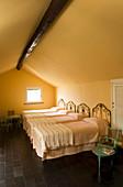 Vier schmiedeeiserne Einzelbetten im Dachzimmer mit schwarzen Fliesenboden