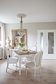 Medallion chairs around dining table in grey-and-white dining room