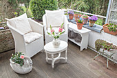 White wicker armchairs and vintage-style coffee table on balcony