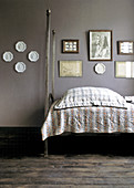 Metal bed below old pictures and decorative plates on grey wall