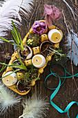 Osterdeko mit Eierkerzen und Blumen in Eierschalen im gelben Eierkarton