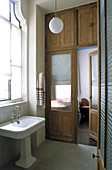 Old wooden door with frosted glass panels and cupboards above in bathroom