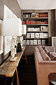 Modern table lamps on rustic table in front of bookshelves