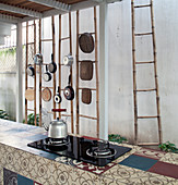 Hob on island counter covered in various tiles in front of ladders used as storage
