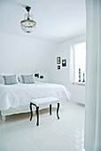 Stool with white upholstery and black legs in white bedroom