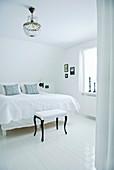 Polsterhocker mit schwarzen Füßen im weißen Schlafzimmer