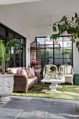 Korbmöbel und Teppich mit Blattmotiv auf überdachter Terrasse
