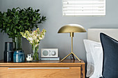 Golden table lamp, radio and vases of flowers and leaves on bedside table