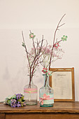 Fabric flowers on twigs in bottles decorated with fabric trim