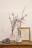 Zweige mit Stoffblumen in Flaschen mit Stoffborten