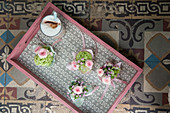 Small posies on tray on old tiled floor