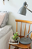 Grey anglepoise lamp and small plant on old chair used as bedside table