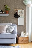 Vintage-style floral wallpaper behind grey sofa