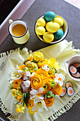 Opulent spring bouquet of ranunculus, tulips and narcissus, bowl of yellow and blue Easter eggs and cup of tea