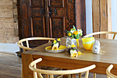 Yellow crockery, Easter wreaths on napkins, sachets with rabbit motifs and posy of flowers