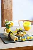 Yellow plate and yellow plate and yellow and white striped napkins with Easter wreaths, posy in jug