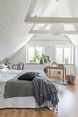 Attic bedroom with white wood panelling