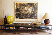 Table lamp and vase on vintage console table below artwork on wall