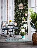 Bistrotisch mit zwei Stühlen und Blumenständer auf der Terrasse