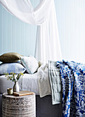Bed with canopy, pillows and blankets, next to it a teak bedside table