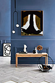 Console table with decorative objects, magazine holder, pendant lamp and artwork on a blue wall