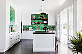 Kitchen island in white kitchen with green wall tiles