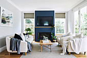 Bright living room with upholstered furniture, fireplace and television on a blue wall