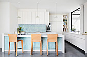 Kitchen counter with turquoise blue mosaic tiles and leather bar stools