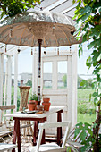Balinese parasol over table on trestles in conservatory in garden