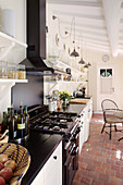 Gas cooker and terracotta floor tiles in narrow country-house kitchen