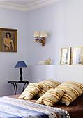Braun gestreifte Kissen auf dem Bett vor hellblauer Wand mit Sockel