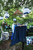 Set table below white and blue lanterns in garden