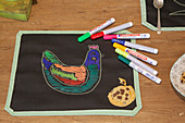 Colourful chicken drawn on place mat made from chalkboard fabric