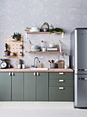 Kitchen base cabinet with green front, open shelves above