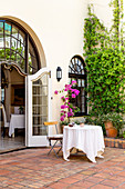 Table with white tablecloth in Mediterranean courtyard with terracotta floor tiles