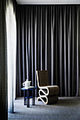 Designer chair and side table with teapot in front of a dark curtain