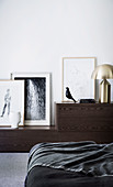 Art work sideboard and bed with black blanket in bedroom