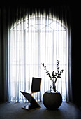 Zig-Zag chair and side table with glass vase in front of arched window with curtain