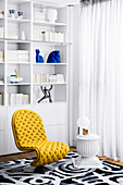 Yellow designer chair and side table against white shelf in living room