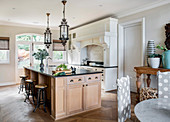 Barstools at large island counter in open-plan kitchen