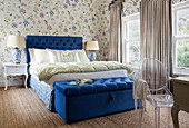 Double bed with royal-blue headboard and ottoman in bedroom with floral wallpaper