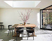Black chairs around wooden table below skylight in dining room