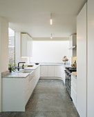 White, minimalist kitchen with rounded corner and concrete floor