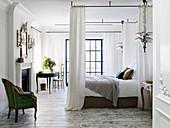 Schlafzimmer mit französischem Sessel, Doppelbett, Kamin und Schreibtisch