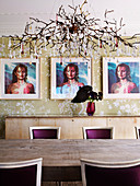 Designer lamp over long dining table with bordeaux-red upholstered chairs, triptych portrait on the wall