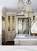 Antique chandelier over kitchen island with marble countertop