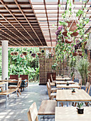 Large terrace with tables, chairs and benches, surrounded by wooden grids for privacy