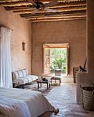 Sitzplatz vor dem Fenster im Schlafzimmer mit Lehmwänden